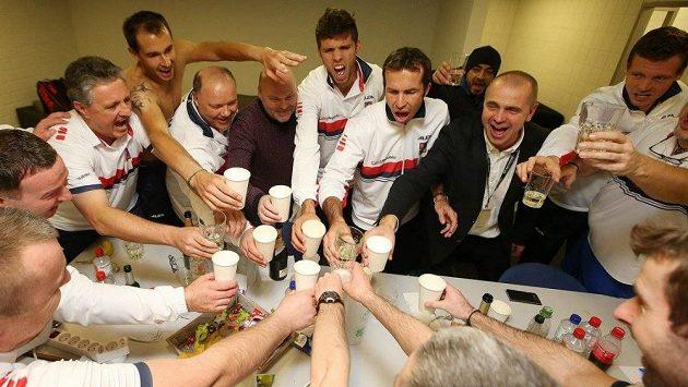 Čeští tenisté oslavují s realizačním týmem postup přes německo v davisově poháru.