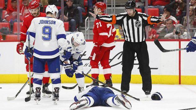 Obránce Tampy Bay Dan Girardi leží na ledě poté, co ho zasáhl projektil z hokejky českého útočníka Detroitu Martina Frka (zcela vlevo).
