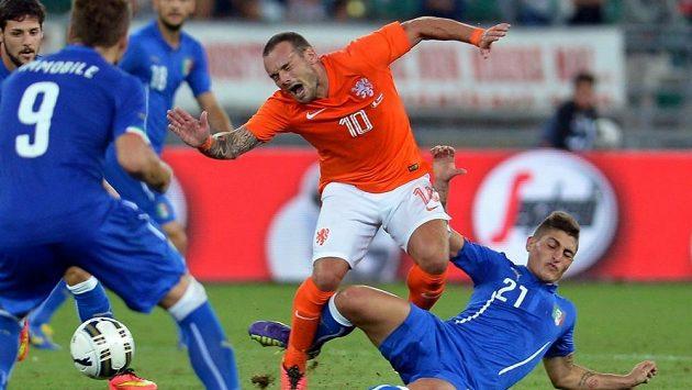 Nizozemec Wesley Sneijder padá po zákroku Marka Verrattiho (vpravo) z Itálie v přípravném utkání obou celků v Bari.