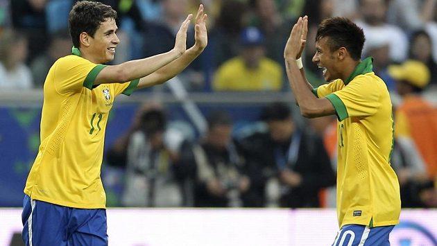 Brazilci Oscar (vlevo) s Neymarem oslavují gól v síti Francie.