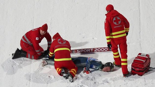 Záchranáři poskytují první pomoc americkému skokanovi Nicholasi Fairallovi po jeho pádu v Bischofshofenu.