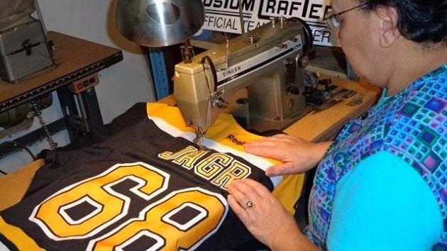 Šikovné ruce švadleny tvoří dres Bruins pro Jaromíra Jágra.
