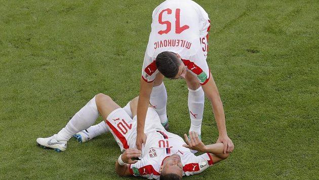 Srbský fotbalista Dušan Tadič, hrající Premier League za Southampton) se svíjí na zemi během utkání MS s Kostarikou. Pomoci se mu snaží spoluhráč Nikola Milenkovič.