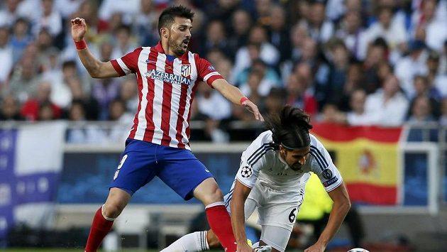 David Villa z Atlétika (vlevo) bojuje o míč se Samim Khedirou z Realu.