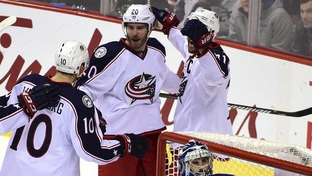 Hokejisté Columbusu se radují ze vstřelené branky Brandona Saada (uprostřed) v zápase proti Vancouveru.