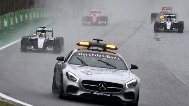 Jezdci krouží na mokré trati v Interlagosu za zpomalovacím vozem.