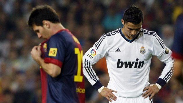 Hvězdy Barcelony a Realu Madrid Lionel Messi a Cristiano Ronaldo se míjí na trávníku při El Clásicu.