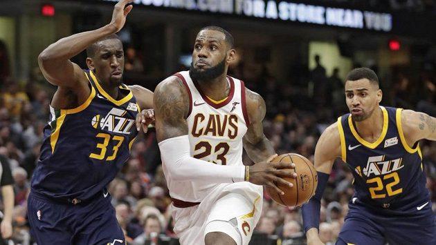 Clevelandský LeBron James uniká Udohovi (33) a Sefoloshovi (22) z Utahu.