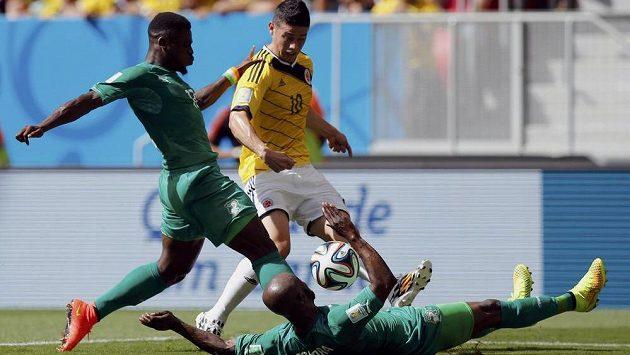 Kolumbijec James Rodriguez (vpravo) bojuje se Sergem Aurierem (vlevo) a Didierem Zokorou (na zemi) z Pobřeží slonoviny.