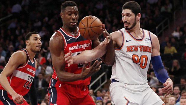 Enes Kanter (vpravo) z New York Knicks bojuje o míč s Ianem Mahinmim z Washingtonu. Přihlíží Otto Porter Jr.