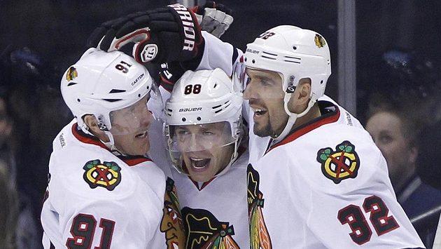 Patrick Kane (uprostřed) slaví gól do sítě Winnipegu. Zleva mu gratuluje Brad Richards, zprava pak Michal Rozsíval. Kane se díky dvěma bodům dostal do čela kanadského bodování NHL.