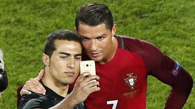 Portugalský kapitán Cristiano Ronaldo se fotografuje se šťastným fanouškem po zápase s Rakouskem.