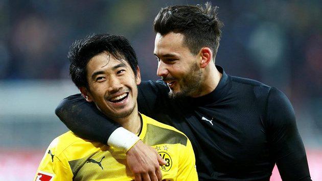 Dortmundští fotbalisté Shinji Kagawa a Roman Bürki slaví výhru nad Mohučí. BVB zvítězilo v bundeslize po osmi zápasech.