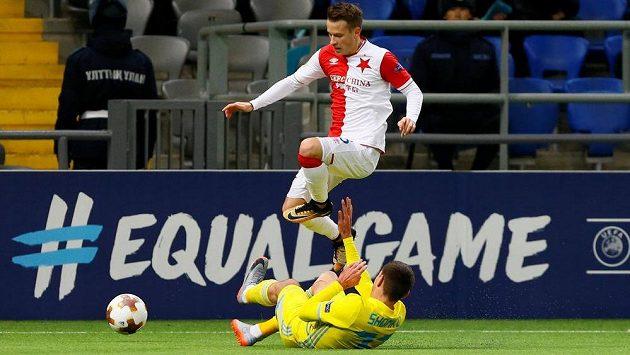 Fotbalista Slavie Jan Sýkora v akci, přeskakuje Dmitrije Šomka z Astany v utkání Evropské ligy.