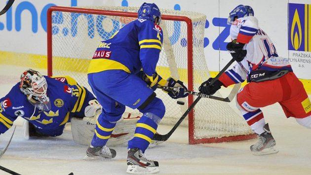 Český útočník Jan Kovář (vpravo) se snaží překonat švédského brankáře Johana Gustafssona (vlevo). Přihlíží obránce Staffan Kronwall.