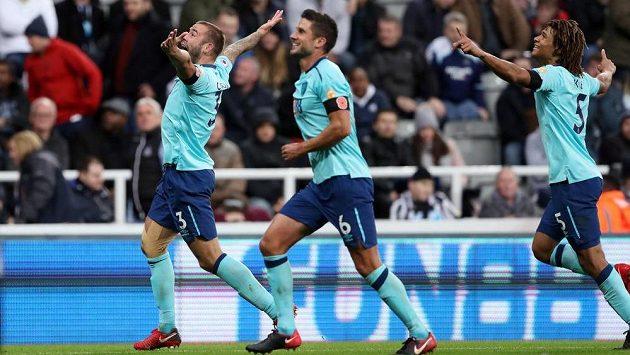 Střelec vítězného gólu Bournemouthu Steve Cook slaví se spoluhráči Andrew Surmanem a Nathanem Akem slaví na St. James Parku. Díky jeho trefě mohla slavit miliónovou výhru i 58 letá Angličanka.