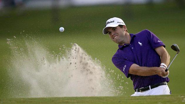 Americký golfista Martin odpaluje míček z písku při 18. jamce Zurich Classic.
