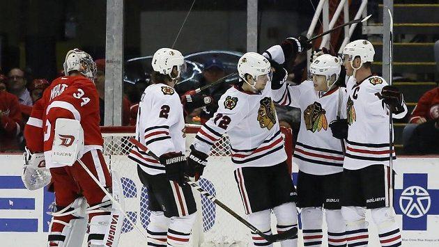 Hokejisté Chicaga se radují po jedné z branek, kterou vstřeli Petrovi Mrázkovi z Detroitu (vlevo).