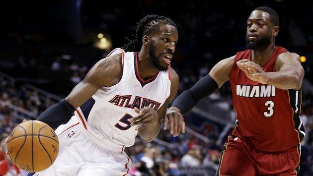 Basketbalista DeMarre Carroll z Atlanty Hawks je bráněn Dwyanem Wadem z Miami.