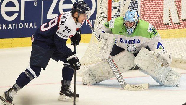 Slovenský hokejista Libor Hudáček se snaží překonat slovinského gólmana Roberta Kristana.