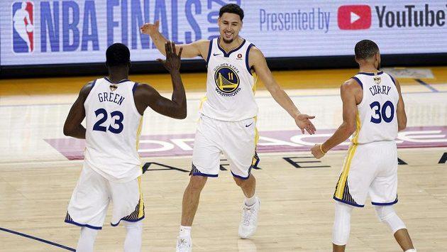 Basketbalisté Golden State Warriors Klay Thompson (11), Draymond Green (23) a Stephen Curry (30) v úvodním finále play off NBA.