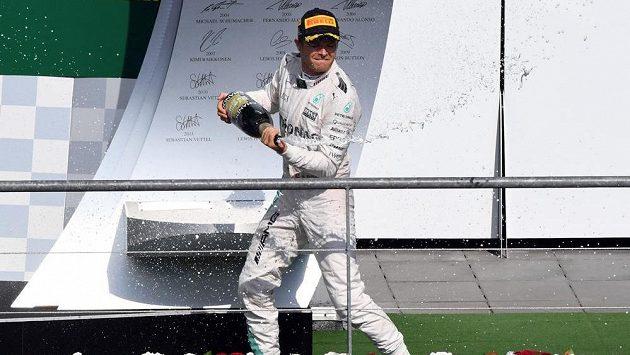 Nico Rosberg oslavuje se šampaňským své vítězství ve Velké ceně Belgie.