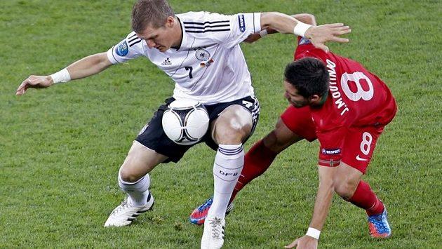 Bastian Schweinsteiger (vlevo) si kryje míč před dotírajícím Portugalcem Joaem Moutinhem