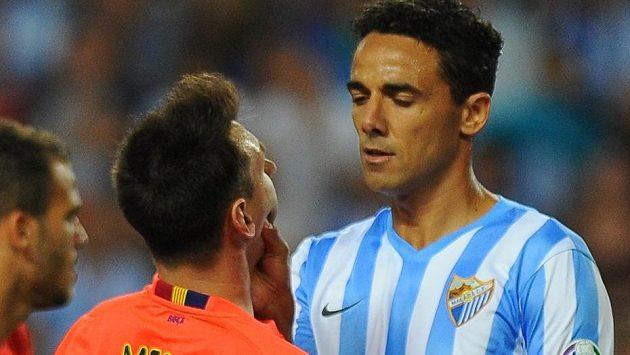 Obránce Málagy Weligton Oliveira drží pod krkem Lionela Messiho.