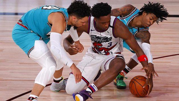 Dillon Brooks z týmu Memphis Grizzlies (vlevo) a jeho spoluhráč Ja Morant (vpravo) bojují o míč se soupeřem z Toronta Raptors.