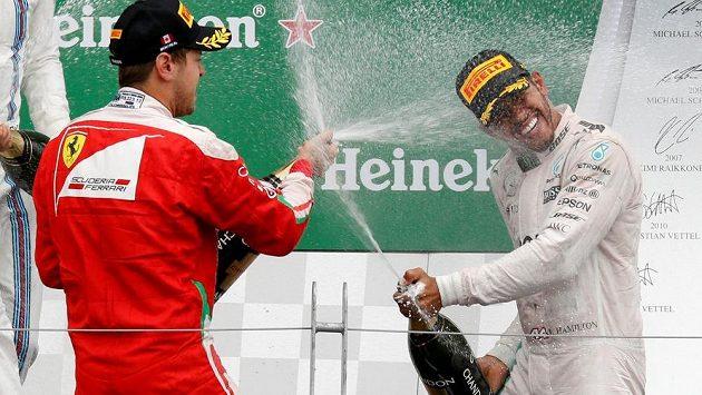 """Po souboji na trati """"přestřelka"""" šampaňským. Vítěz GP Kanady Lewis Hamilton (vpravo) a druhý Sebastian Vettel na stupních vítězů v Montrealu."""
