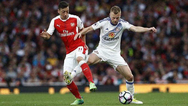 Mesut Özil (vlevo) z Arsenalu v souboji se Sebastianem Larssonem ze Sunderlandu.