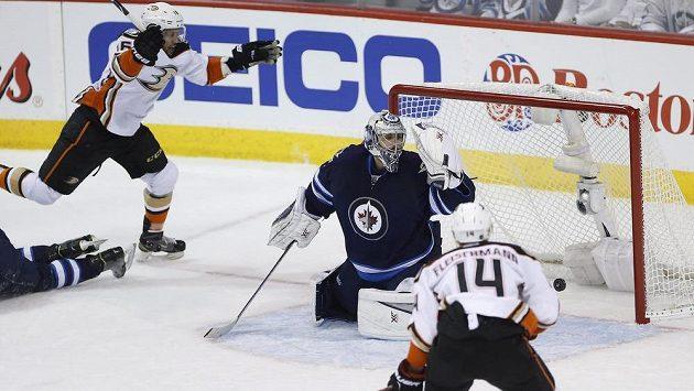 Hokejista Anaheimu Ducks Emerson Etem překonává brankáře Winnipegu Ondřeje Pavelce. Tomáš Fleischmann (vpravo) přihlíží, jak puk končí v síti.