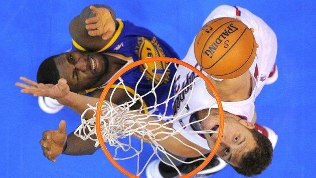 Losangelský Blake Griffin dává koš přes Festuse Ezeliho z týmu Warriors.
