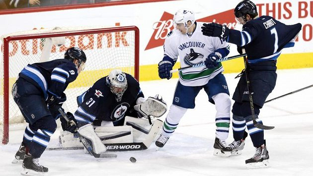 Ondřej Pavelec v brance Winnipegu řeší za asistence spoluhráčů šanci křídelníka Vancouveru Alexe Burrowse.