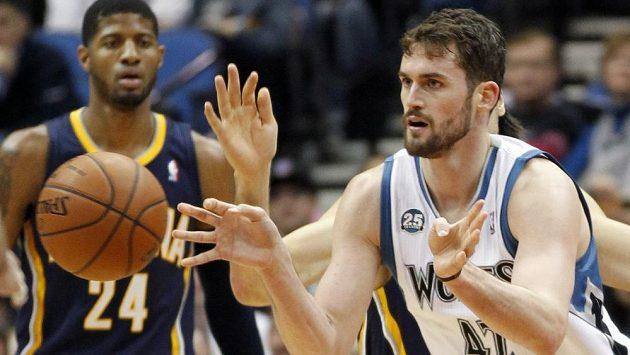 Kevin Love (42) z Minnesoty v utkání NBA s týmem Indiana Pacers, jeho akci přihlíži Paul George (24).