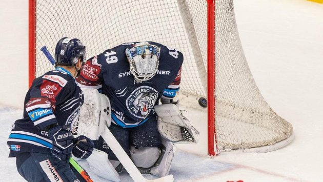 Liberecký hokejista Michal Bulíř sleduje, jak zasahuje v brance jeho spoluhráč Dominik Hrachovina. Všemu přihlíží Wojciech Wolski z Třince.