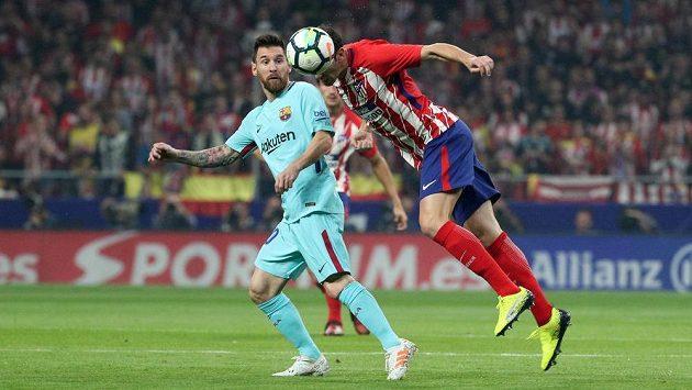 Klenot Barcelony Lionel Messi (vlevo) bojuje o míč s Diegem Godínem z Atlétika Madrid.