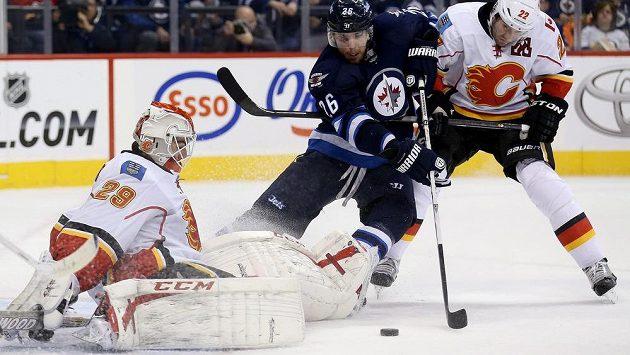 Brankář Calgary Flames Reto Berra (29) v jednom z mnoha soubojů s útočníkem Winnipegu Blakem Wheelerem (26).