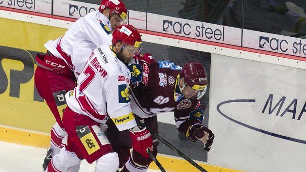 Zleva Lukáš Gavlas a Martin Růžička (oba Třinec) bojují o kotouč s Tomášem Rolinkem (Sparta).