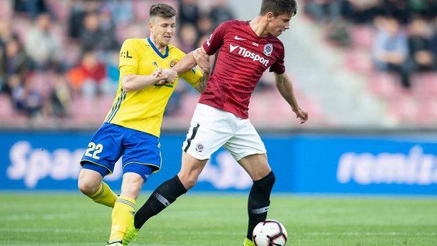 Lukáš Bartošák v dresu Zlína a Adam Hložek ze Sparty během ligového utkání v Praze.