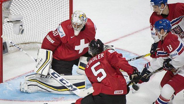 Čeští hokejisté Michael Špaček (18) a Adam Musil (26) se tlačí před švýcarského gólmana Jorena Van Pottelberghea (30), jemuž pomáhá Livio Stadler (5).