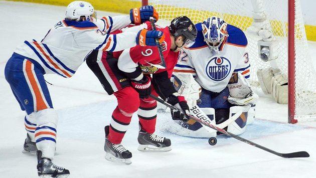 Ottawský útočník Milan Michálek (uprostřed) se snaží překonat brankáře Edmontonu Richarda Bachmana. Vlevo je obránce Olejářů Jeff PEtry.