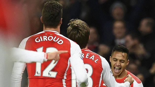 Střelci Alexisovi Sánchezovi (vpravo) běží pogratulovat ke gólu jeho spoluhráči z Arsenalu Nacho Monreal (uprostřed) a Olivier Giroud.
