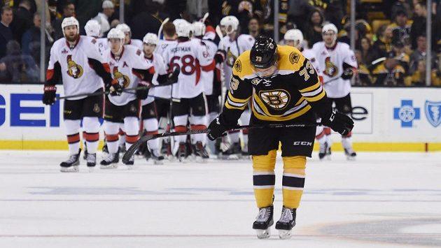 Radost hokejistů Ottawy po výhře ve čtvrtém utkání 1. kola play off s Bostonem, vpředu zklamaný obránce domácích Charlie McAvoy.
