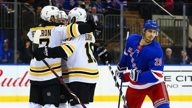 David Pastrňák přijímá gratulace od spoluhráčů z Bostonu po gólu proti New York Rangers. Vpravo útočník domácích Chris Kreider.