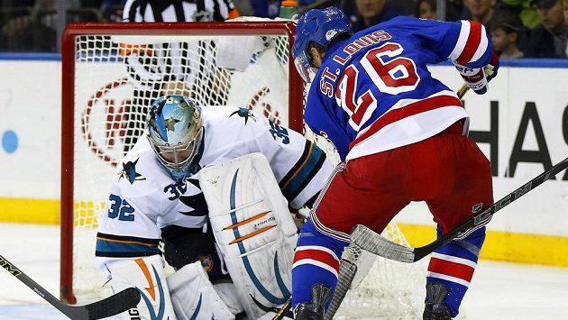 Útočník Rangers Martin St. Louis překonává gólmana San Jose Alexe Stalocka.