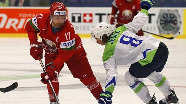 Slovinský hokejista Žiga Jeglič (vpravo) bojuje o puk s Bělorusem Alexejem Kaljužným v utkání MS.