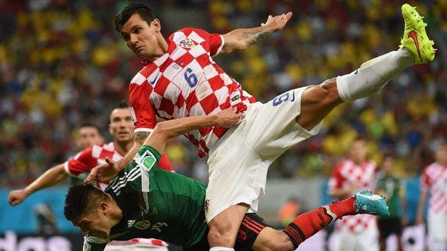 Chorvatský zadák Dejan Lovren (vpravo) na světovém šampionátu v Brazílii v souboji s Mexičanem Oribem Peraltou.