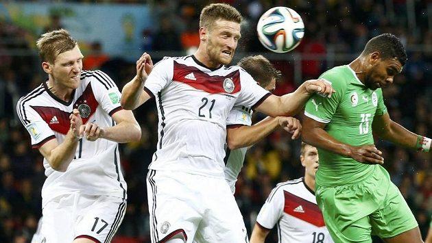 Němečtí obránci Per Mertesacker (vlevo) a Shkodran Mustafi (druhý zleva) odvrací míč před dotírajícím Arbím Hilálem Súdáním z Alžírska.