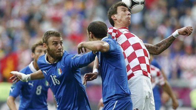 Chorvat Mario Mandžukič (vpravo) v obležení Italů De Rossiho (vlevo) a Chielliniho